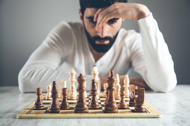 Thinking man playing chess on table