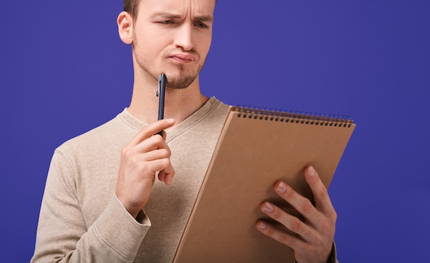 Thinking man with brown paper notebook looks at page