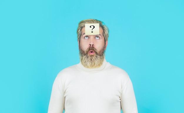 青い背景に疑問符を持つ思考の男。額にクエスチョンマークが付いた男が見上げています。疑問符の付いた紙のメモ。頭のひげの男の疑問符、解決策の問題
