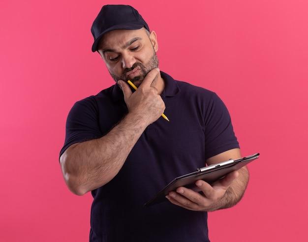 Думающий курьер средних лет в униформе и кепке держит и смотрит в буфер обмена, схватившись за подбородок, изолированный на розовой стене