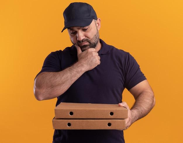 Думающий курьер среднего возраста в униформе и кепке держит и смотрит на коробки из-под пиццы, схватившись за подбородок, изолированный на желтой стене