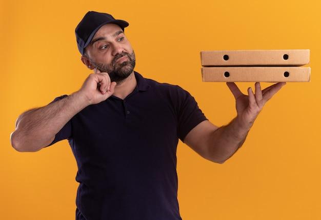 Думающий курьер среднего возраста в униформе и кепке держит и смотрит на коробки для пиццы, положив палец на щеку, изолированную на желтой стене