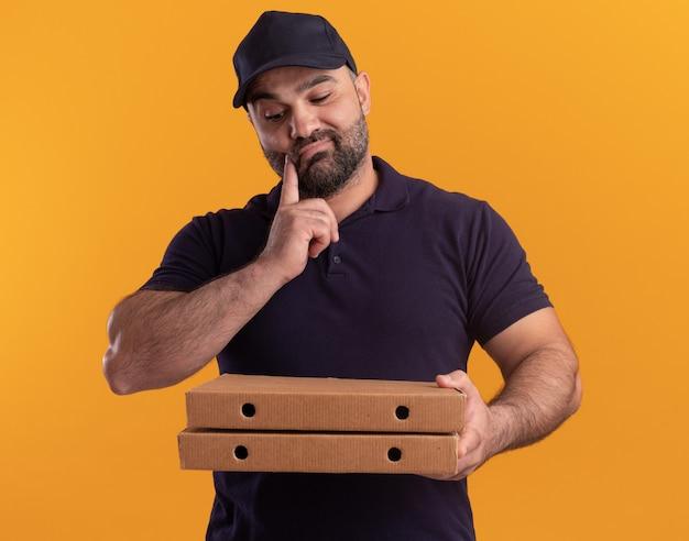 Uomo di consegna di mezza età di pensiero in uniforme e cappuccio che tiene e che esamina le scatole della pizza che mettono il dito sulla guancia isolata sulla parete gialla