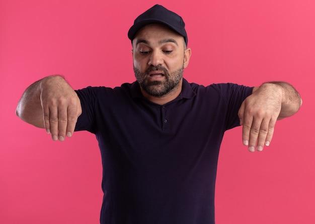 Uomo di consegna di mezza età di pensiero in uniforme e berretto che finge di tenere qualcosa di isolato sul muro rosa