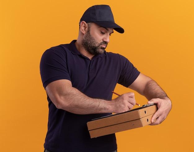 Uomo di consegna di mezza età di pensiero in uniforme e cappuccio che scrive qualcosa sugli appunti sulle scatole della pizza isolate sulla parete gialla
