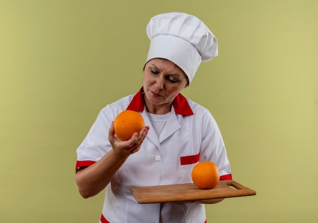 Thinking middle-aged female cook in chef uniform holding orange on cutting board and looking at orange in her hand