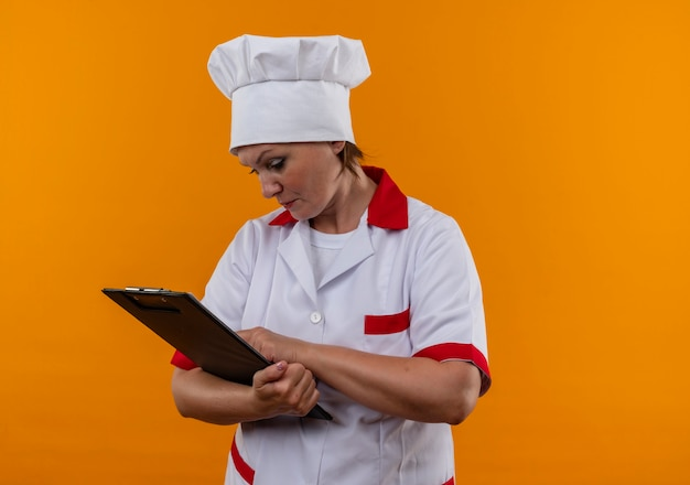 Thinking middle-aged female cook in chef uniform looking at clipboard in her hand  with copy space