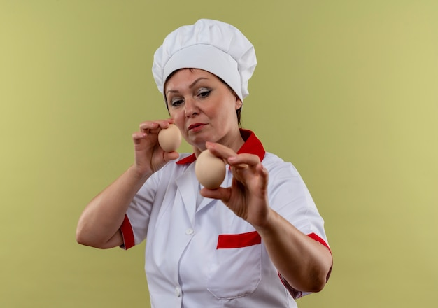 Thinking middle-aged female cook in chef uniform looking at eggs in her hand