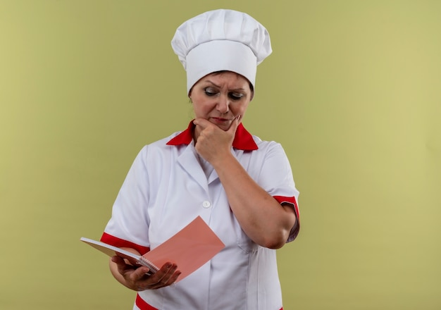 Thinking middle-aged female cook in chef uniform looking at notebook in her hand and put her hand on cheek  with copy space