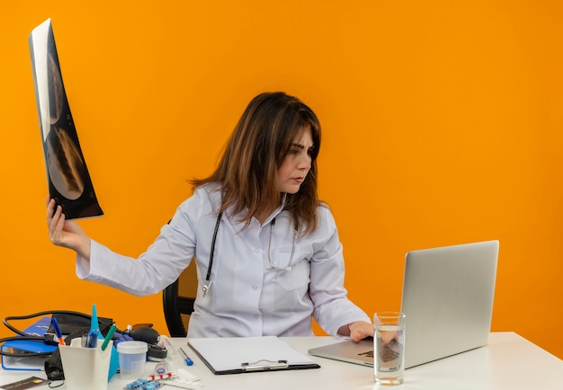 X線を保持し、孤立したオレンジ色の壁にラップトップを見て医療ツールでラップトップで机の仕事に座っている聴診器で医療ローブを着て考える中年女性医師