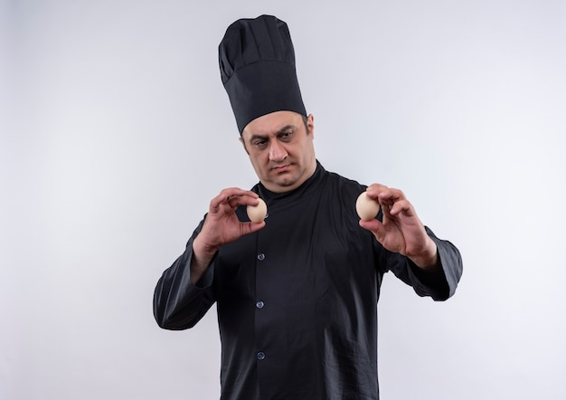 Thinking middle-aged male cook in chef uniform holding eggs with copy space