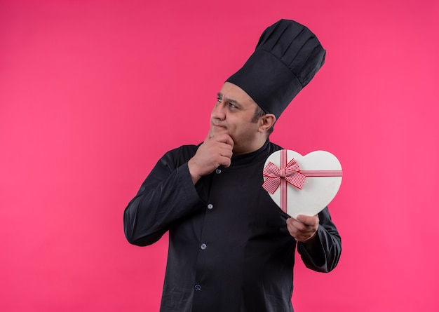 Thinking middle-aged male cook in chef uniform holding heart shape box with copy space