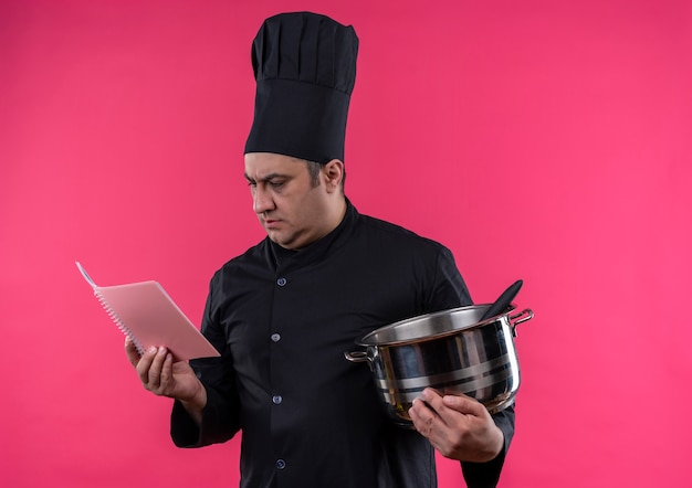 Thinking middle-aged male cook in chef uniform holding saucepan looking at notebook in his hand