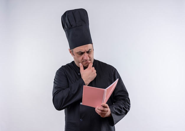 Thinking middle-aged male cook in chef uniform looking at notebook in his hand