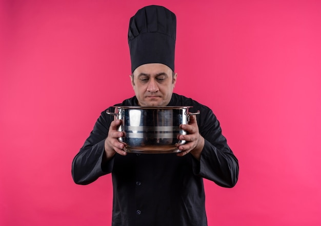 Thinking middle-aged male cook in chef uniform looking at saucepan in his hand with copy space