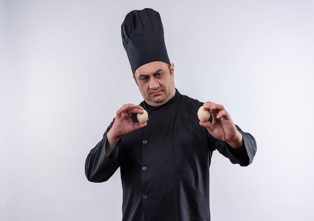 コピースペースで卵を保持しているシェフの制服を着た中年男性料理人を考える