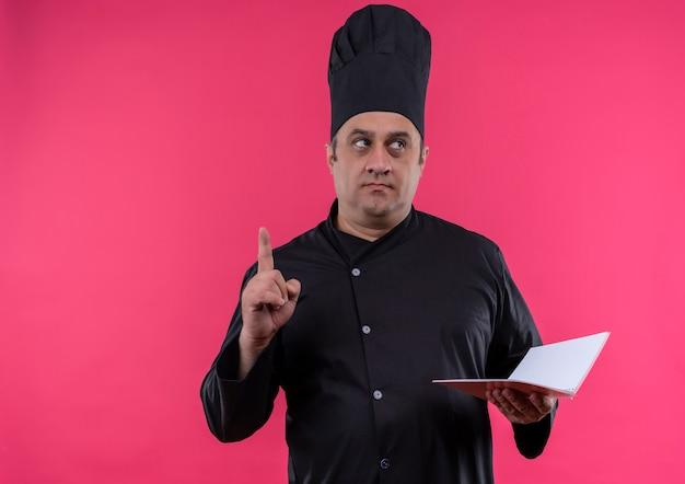 ノートブックを持ったシェフの制服を着た中年男性料理人がコピースペースで指を上に向けている