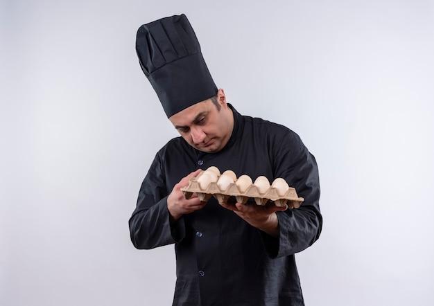 彼の手で卵のバッチを見てシェフの制服を着た中年男性料理人を考える