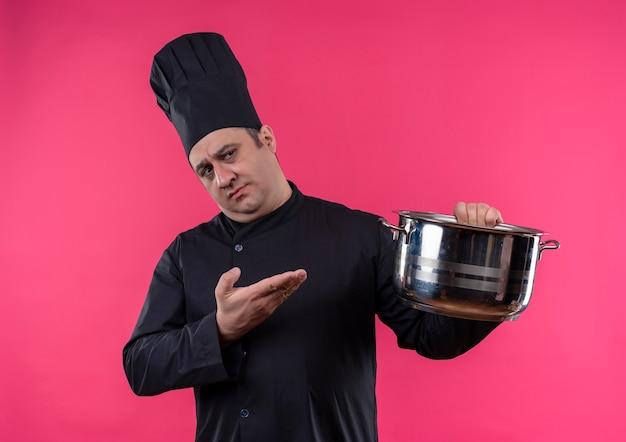 手に鍋を見せてシェフの制服を着た中年男性料理人を考える