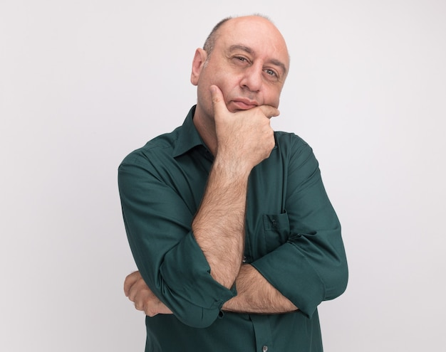 Thinking middle-aged man wearing green t-shirt grabbed chin isolated on white wall