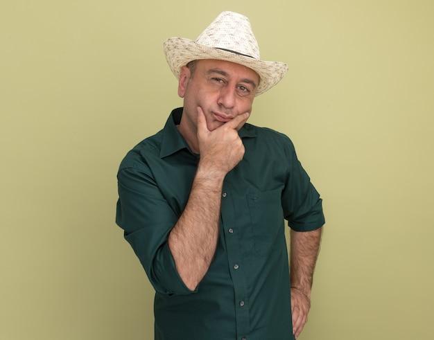Pensando un uomo di mezza età che indossa la maglietta verde e il cappello ha afferrato il mento mettendo la mano sulla vita isolata sulla parete verde oliva