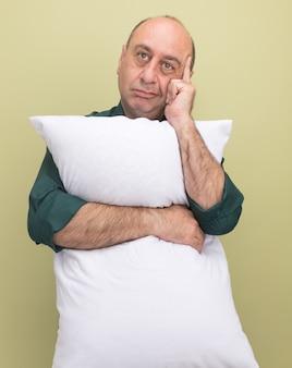 緑のtシャツを着て考えている中年男性はオリーブグリーンの壁に隔離された寺院に指を置く枕を抱きしめました