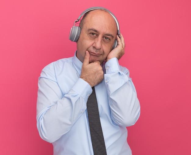 Думающий мужчина средних лет в белой футболке с галстуком и наушниками схватился за подбородок на розовой стене