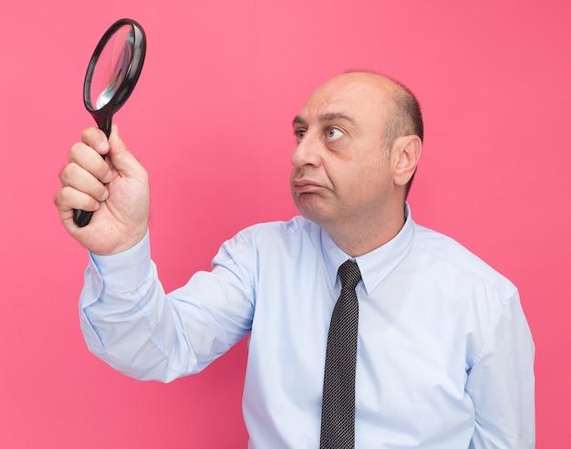 Uomo di mezza età di pensiero che indossa la maglietta bianca con la cravatta che alza e che guarda la lente d'ingrandimento isolata sulla parete rosa
