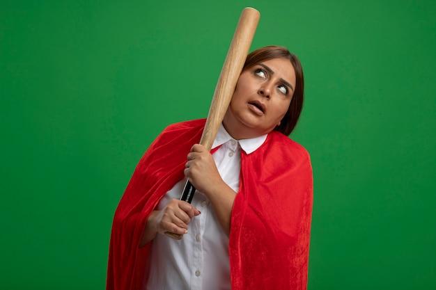 Thinking middle-aged superhero female looking up putting baseball bat on cheek isolated on green background