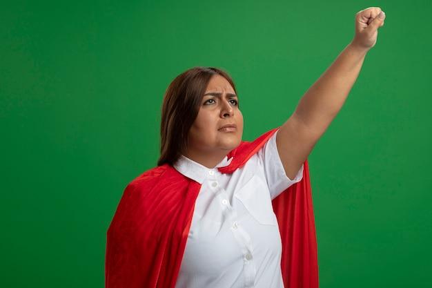 Думая женщина супергероя средних лет, глядя вверх, поднимая кулак, изолированные на зеленом фоне