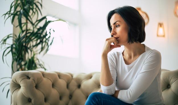 내 생각을 생각합니다. 그녀의 오른손으로 그녀의 턱을 만지고있는 동안 그녀의 현대 아파트에서 소파에 앉아 생각하고 심각한 여자의 클로즈업 사진.