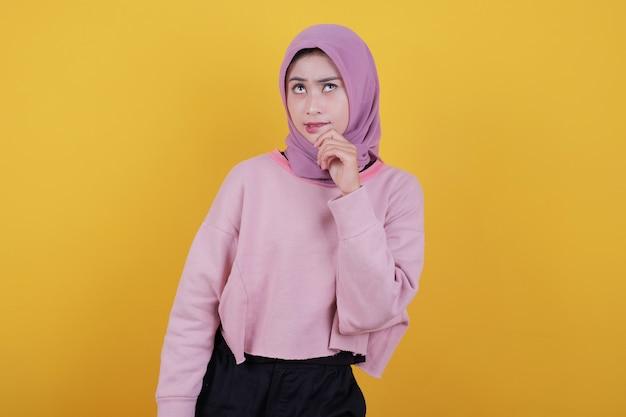 Думая о молодой женщине в повседневной футболке, желтая стена