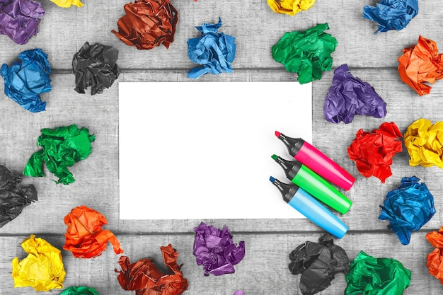 箱の外で考える色とりどりのしわくちゃの紙と木製の背景にカラフルなフェルトペンで白紙の紙のアイデアと新しい革新を打ち破る新しい革新は決してあきらめません