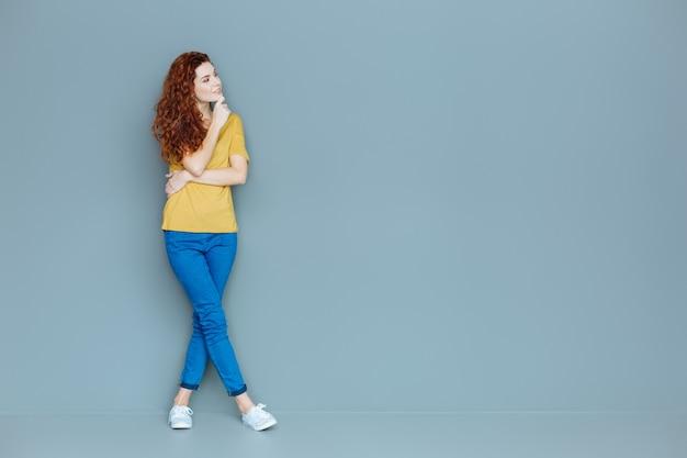 思考プロセス。灰色の背景に立って、彼女の考えに焦点を当てながら彼女のあごを保持しているスマートな素敵な赤い髪の女性