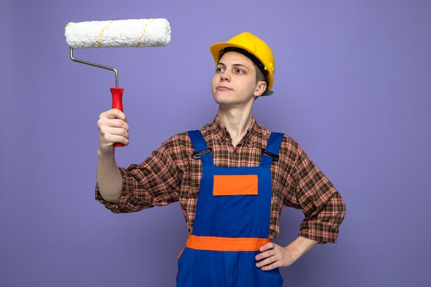 Thinking putting hand on hip young male builder wearing uniform holding and looking at roller brush