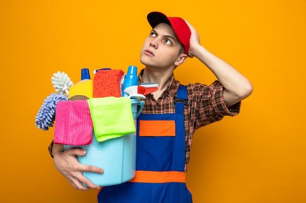 유니폼을 입고 모자를 쓰고 청소 도구 양동이를 들고 있는 젊은 청소 남자의 머리에 손을 대고 생각