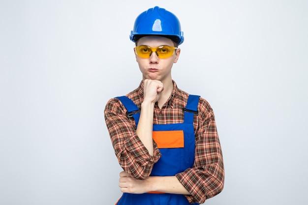 Думая, положив руку под подбородок, молодой мужчина-строитель в униформе и очках