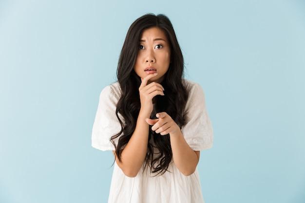 Думая испуганная молодая азиатская красивая женщина позирует изолированной над синей стеной