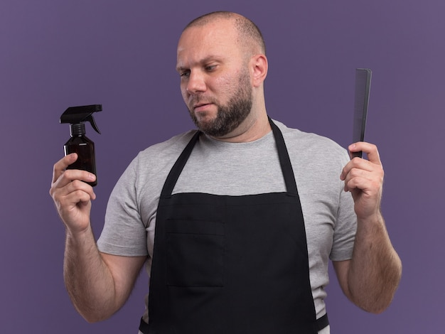 Thinking slavic middle-aged male barber in uniform holding comb and looking spray bottle in his hand isolated on purple wall