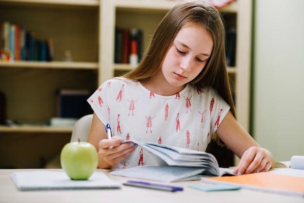Thinking teen girl at desk Free Photo