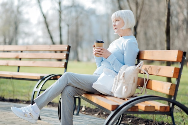 Thinking. thoughtful blond woman drinking coffee while sitting on the bench