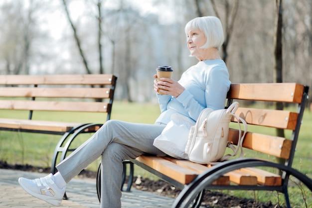 생각. 벤치에 앉아있는 동안 커피를 마시는 사려 깊은 금발 여자