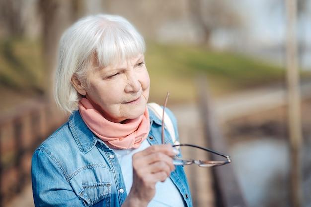 Думаю. задумчивая зрелая женщина держит очки и смотрит вдаль