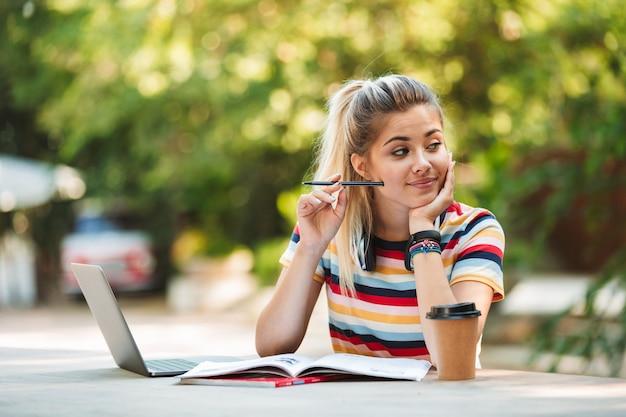 노트를 작성하는 랩톱 컴퓨터를 사용 하여 공원에 앉아 생각 사려 깊은 젊은 귀여운 여자 학생.
