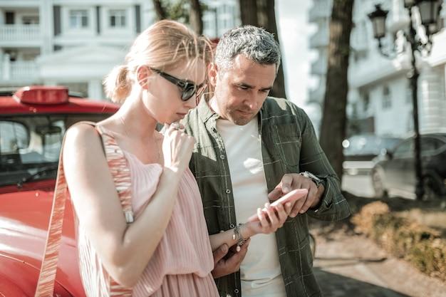 함께 생각합니다. 아내가 새 스마트폰을 사용하는 방법을 이해하도록 돕는 집중된 남자.