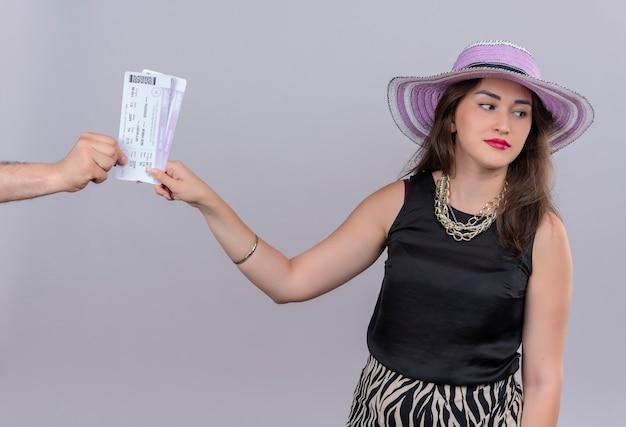 Молодая девушка думает путешественник в черной майке в шляпе, принимая билеты на белом фоне