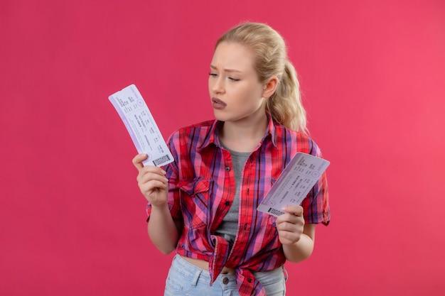 Думающая путешественница молодая девушка в красной рубашке держит билеты на изолированном розовом фоне