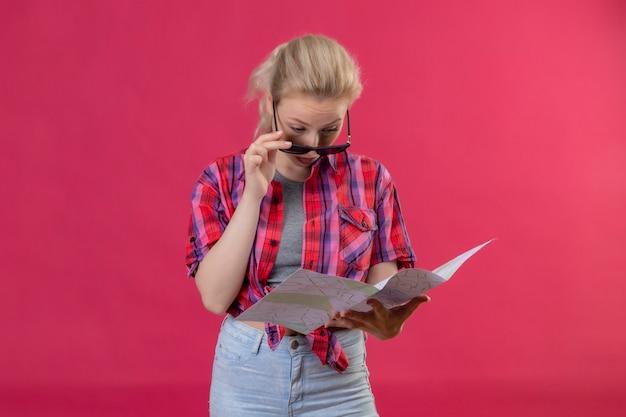 孤立したピンクの背景の地図を見てメガネに赤いシャツを着て旅行者少女を考える