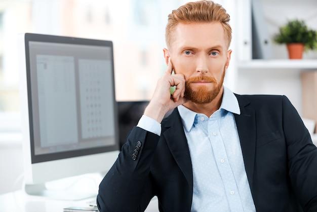 Обдумывает свой следующий бизнес-ход. уверенный молодой бородатый бизнесмен, глядя в камеру, сидя на своем рабочем месте