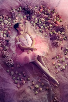 Thinking of warm. top view of beautiful young woman in pink ballet tutu surrounded by flowers. spring mood and tenderness in coral light. art photo. concept of spring, blossom and nature's awakening.